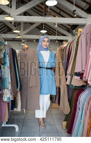 A Woman In A Veil Shop Owner Holding Two Robes To Show While Standing