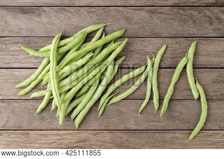 A Group Of Green Bean Pods Over Wooden Table.