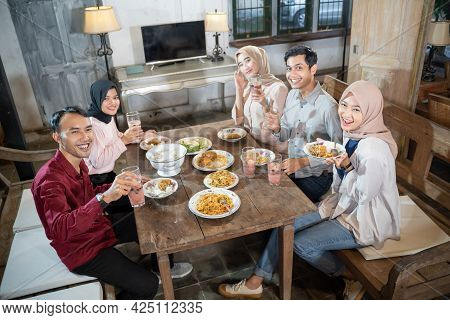 Two Muslim Men And Three Women Wearing Hijab Are Happy To Bring Their Food