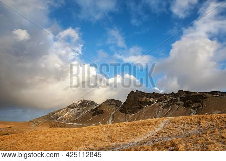 Typical Icelandic landscape of volcanic mountain peaks and rolling hillsides with hiking paths. Winter scene with a dusting of snow in Vik, Southern Iceland.