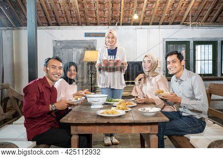Group Of Friends Smiling As They Gather When Breaking Fast Together In The Dining Room