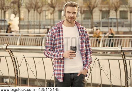Handsome Young Man Wear Headphones. Casual Dressed Male Drinking Morning Coffee From Cup. Unshaven G