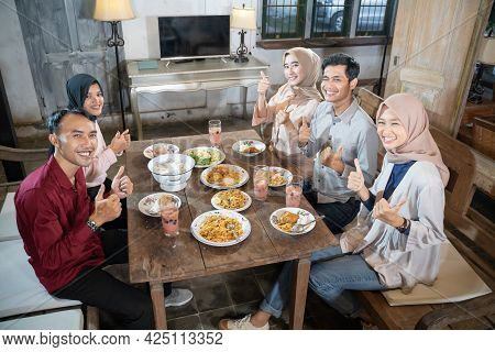 Two Muslim Men And Three Women In Veil Smiling With Thumbs Up