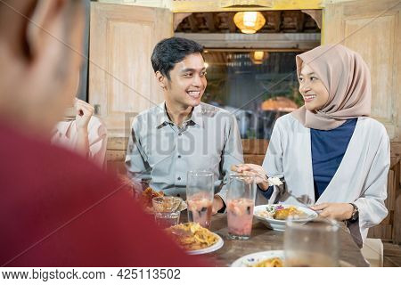A Man And A Woman In Veil Chat While Breaking Their Fast Together