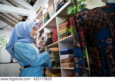 A Veiled Business Woman Neatly Arranges A Pile Of Clothes On A Clothes Rack