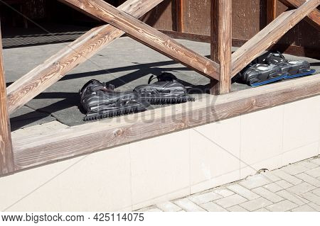 Two Pairs Of Black Skates Lie On A Wooden Terrace. The End Of Skating Season