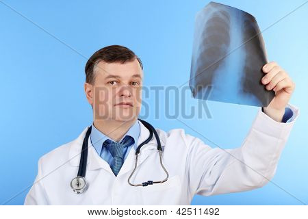 Medical doctor analysing x-ray image  on blue background
