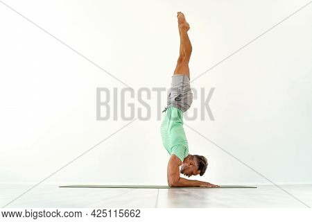 Young Man Acrobatics Gymnastic Doing A Handstand Studio Isolated On White Background, Athletic Sport