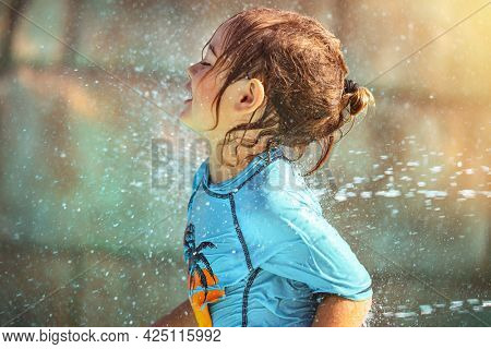 Happy Little Boy Enjoying Refreshing Shower on the Beach. Playing with a Water. Having Fun in Aquapark. Summer Holidays Concept.