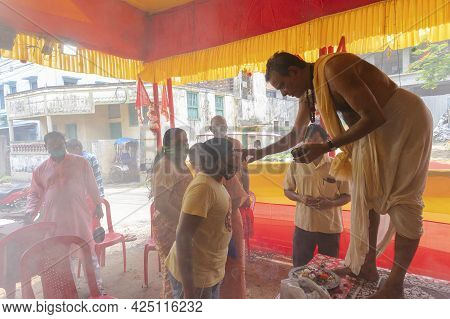 Howrah, West Bengal, India - 29th June 2020 : Hindu Priest Putting Holy Ash Of Yajna On Heads Of Dev