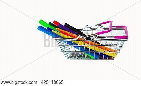 A miniature shopping basket in a supermarket, isolated on a white background, colored markers are depicted in the basket in close-up. A set of markers in the cart. The concept of returning to school