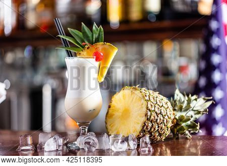 Pina colada coctail on bar counter with fresh pinapple and alcohol bottles.