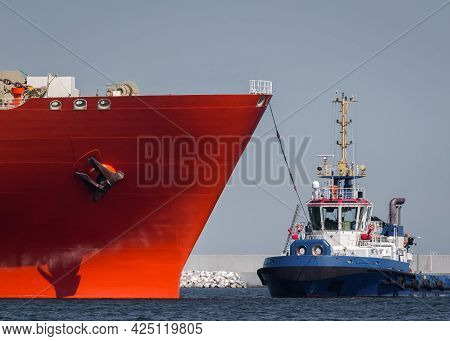 Tugboat And Red Tanker - Ships Maneuver In The Port