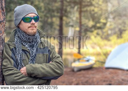 Closeup Portrait Tough Guy Stands Near The Tent And His Kayak In The Forest On The River Bank. Outdo