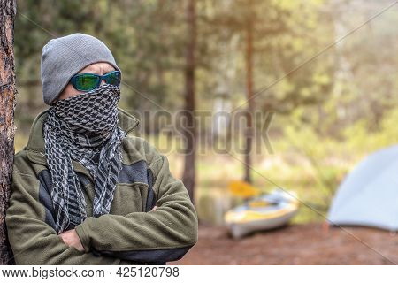 Tough Guy Stands Near The Tent And His Kayak In The Forest On The River Bank. Outdoor Camping Tent C