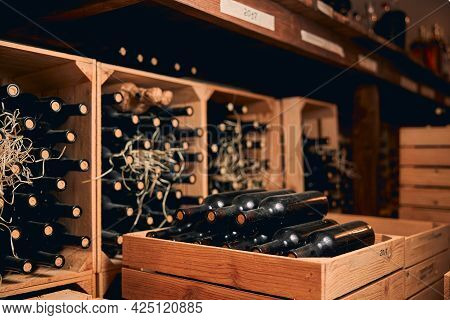 Wine Cellar With Bottles Of Alcoholic Drink In Wooden Crates
