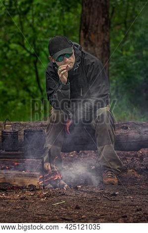 Tough Guy In Black Glasses And Harsh Clothes Smokes A Cigarette Near Forest Bonfire. Outdoor Camping