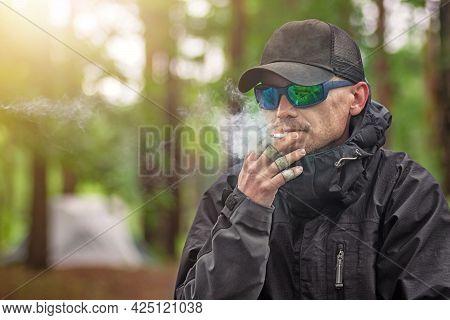Closeup Portrait Tough Guy In Black Glasses And Harsh Clothes Smokes A Cigarette Near Forest Bonfire
