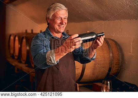 Cheerful Man With Bottle Of Wine Standing In Wine Cellar