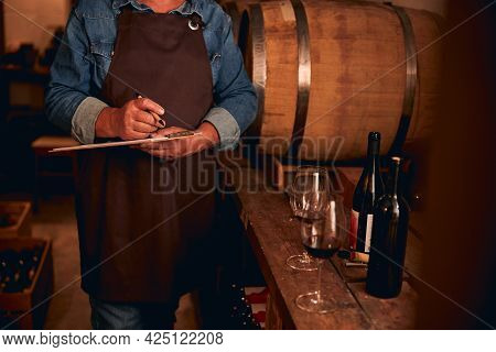 Unrecognized Winery Owner Checking The Quality Of Product