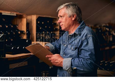 Winery Worker Counting The Quantity Of Bottles Left In Cellar