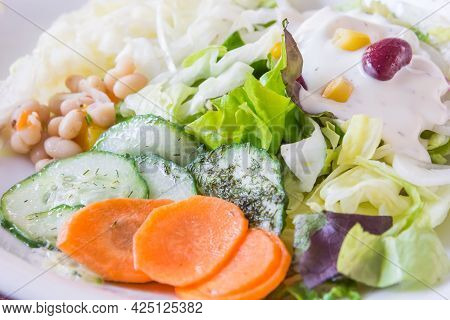 Greek Salad In German Style Served With Carrots, Cabbage, Lettuce And White Beans And Yoghurt Sauce