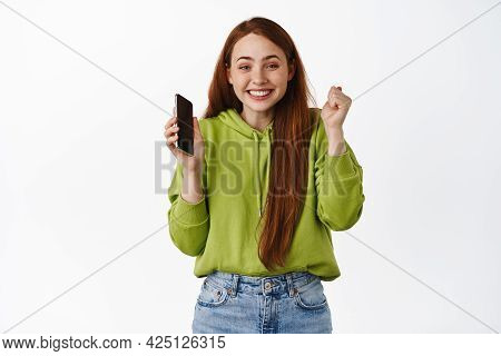 Happy Redhead Girl Rejoice, Holding Smartphone And Celebrating, Winning On Mobile Phone And Triumphi