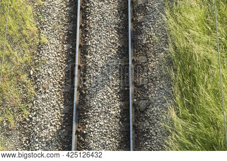 Railway Rails And Concrete Sleepers, Top View. Rails And Sleepers Covered With Gravel