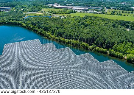 Panorama View On Panels Floating On Water With Floating Solar Panels In A Blue Pond Under The Sunlig
