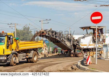 A Crawler Milling Machine Removes The Top Layer Of Asphalt From A Road Section Being Repaired And Lo