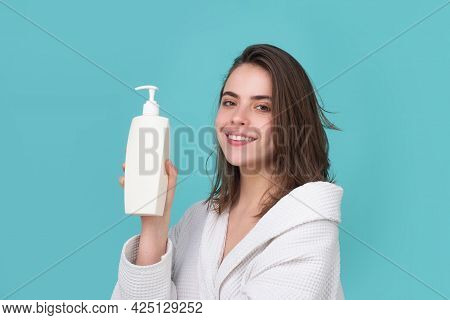A Beautiful Young Girl In The Studio With Wet Hair. Beauty Haircare Cosmetics. Woman Hold Bottle Sha