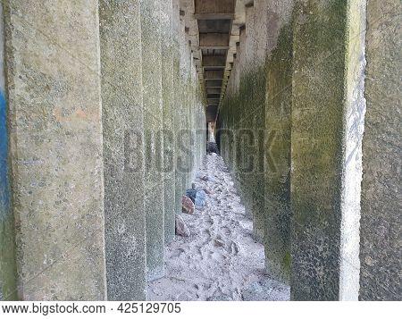 Walkway Between Concrete Pillars.  The Path Over The Stones Is Located Between The Concrete Pillars