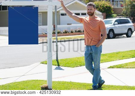 Professional Realtor Real Estate Agent With House For Sale Sign Standing Near Residential Property O