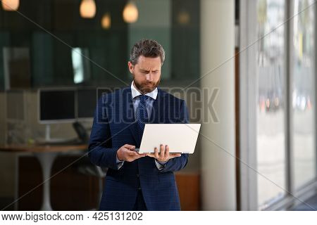 Business Man Holding Laptop Standing On The Street Near Business Office Building.