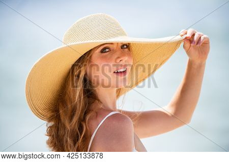 Beautiful Girl With Straw Hat Enjoying Sunbath At Beach. Young Tanned Woman Enjoying Breeze At Seasi