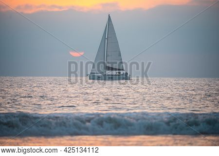 Yacht Sailing Against Sunset. Landscape With Skyline Sailboat And Sunset Silhouette. Yachting Touris
