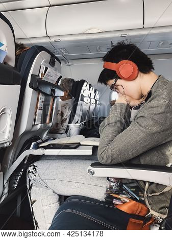 Young Man With Headphones In The Aircraft Cabin. Modern Technology Concept