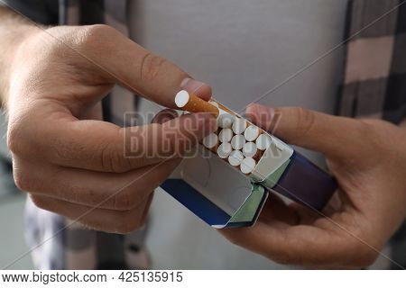 Man Taking Cigarette Out Of Pack, Closeup