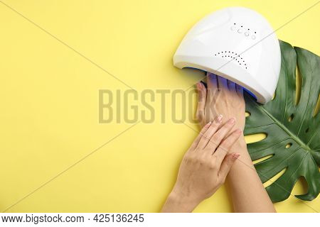 Woman Using Ultraviolet Lamp To Dry Gel Nail Polish On Yellow Background, Top View. Space For Text