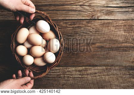 Flat Lay With Hands Holding Basket With Organic Chicken Eggs On Wooden Background. Organic Household