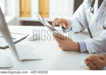 Unknown Male Doctor And Patient Woman Discussing Current Health Examination While Sitting In Clinic