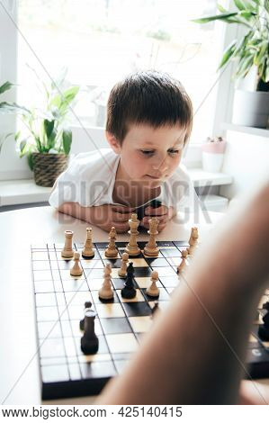 A Cute Caucasian Boy Is Thinking About The Next Move In A Board Game. Chess For The Development Of L