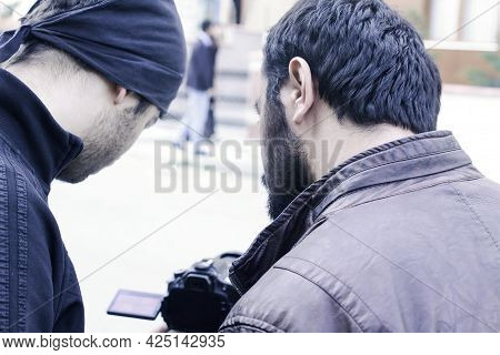 Rear View Of Two Professional Young Men From Film Crew Looking At Camera Screen While Shooting A Mov