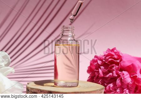 Bottle Of Cosmetic Essential Oil With Dropper On A Wood Cut. Serum Oil Is Dripping From Dropper. Bea
