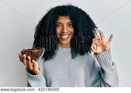 African american woman with afro hair holding raisins in bowl doing ok sign with fingers, smiling friendly gesturing excellent symbol
