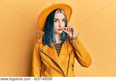 Young modern girl wearing yellow hat and leather jacket mouth and lips shut as zip with fingers. secret and silent, taboo talking