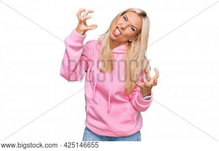 Young blonde woman wearing casual sweatshirt shouting frustrated with rage, hands trying to strangle, yelling mad