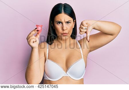 Beautiful brunette woman holding menstrual cup wearing underwear thinking attitude and sober expression looking self confident