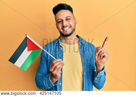 Young arab man holding palestine flag smiling happy pointing with hand and finger to the side