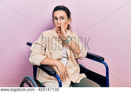Young hispanic woman sitting on wheelchair hand on mouth telling secret rumor, whispering malicious talk conversation